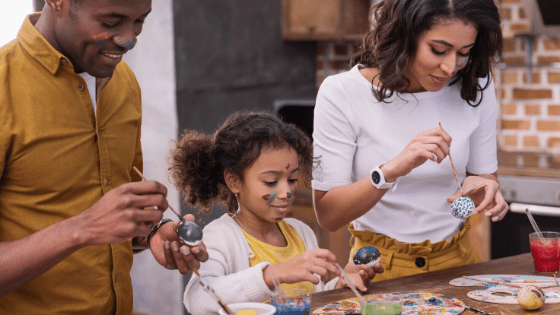 Parents painting with daughter
