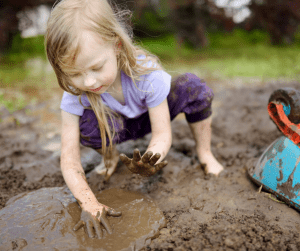 Little Girl Playing in Mud