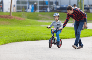 Dad helping small child ride a bike